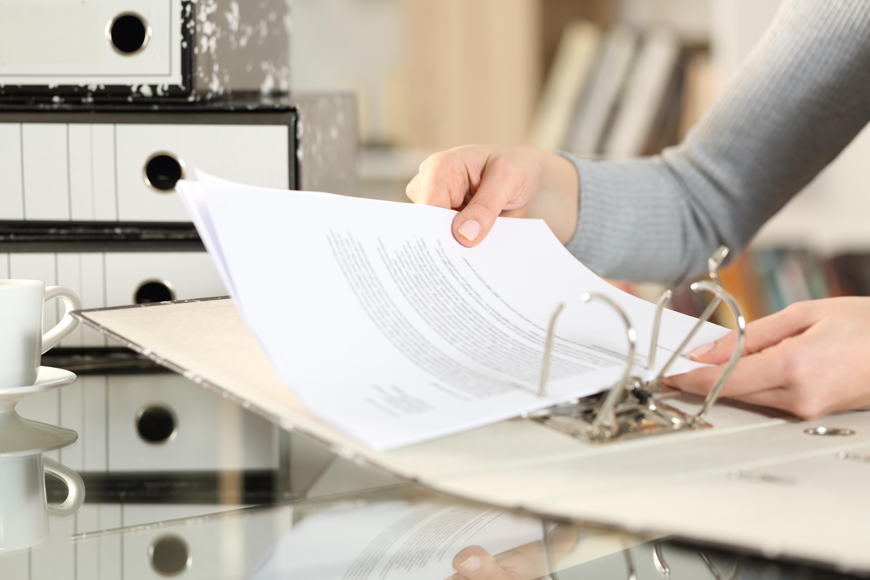Frauen Hand legt Mietvertrag in Ordner ab