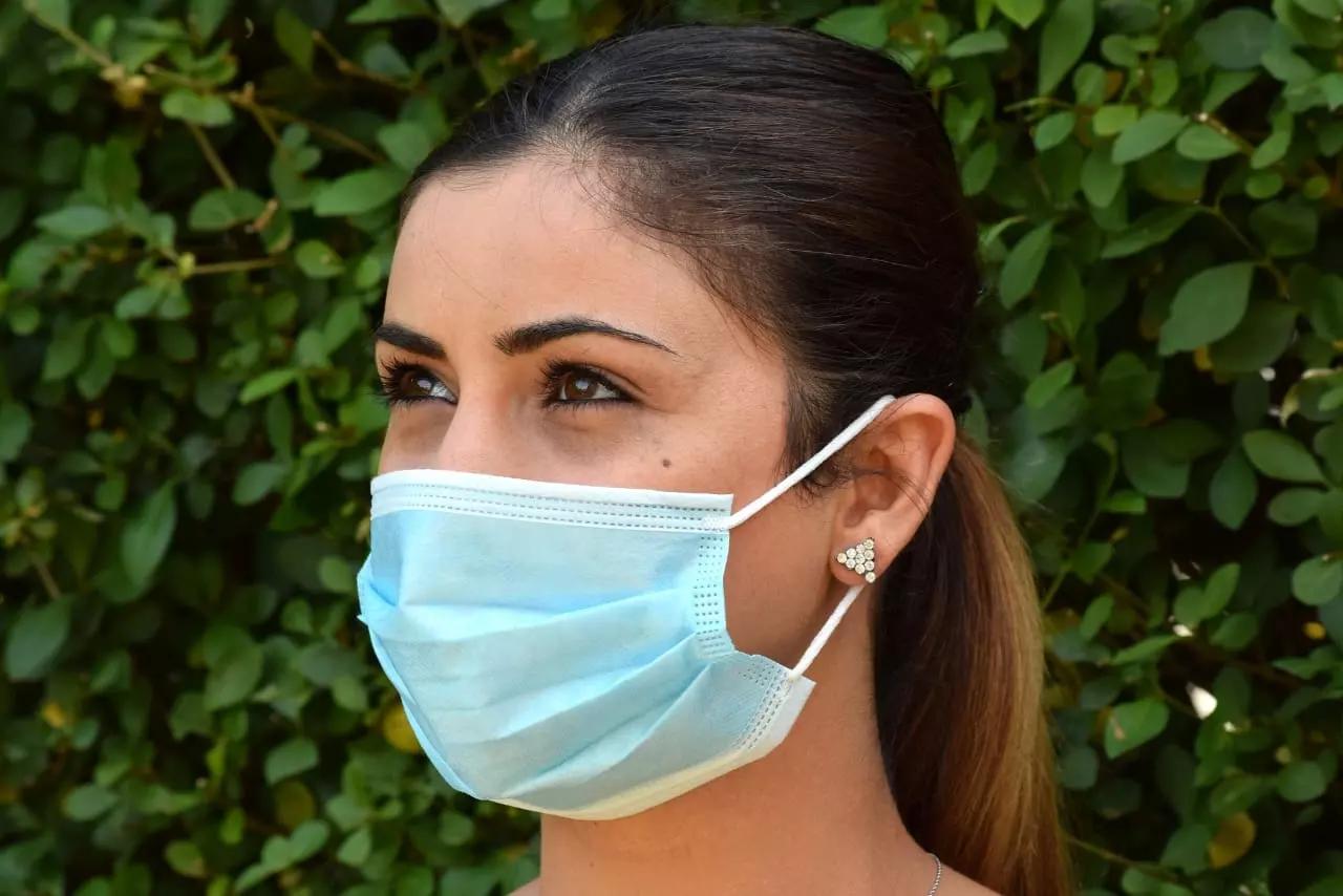 Frau mit Maske hinter einer Hecke