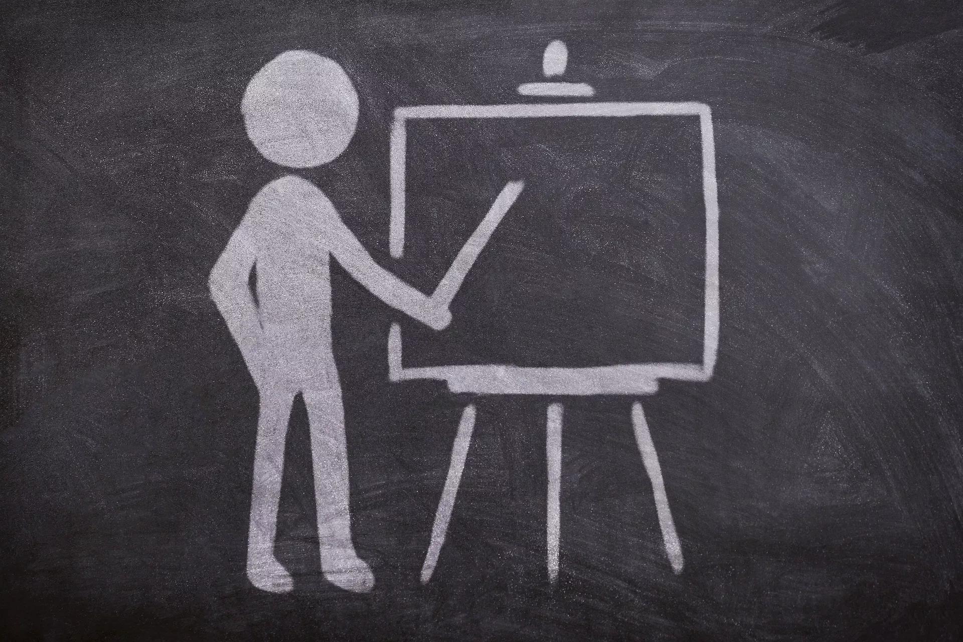 Lehrer mit Zeigestab an einer Tafel